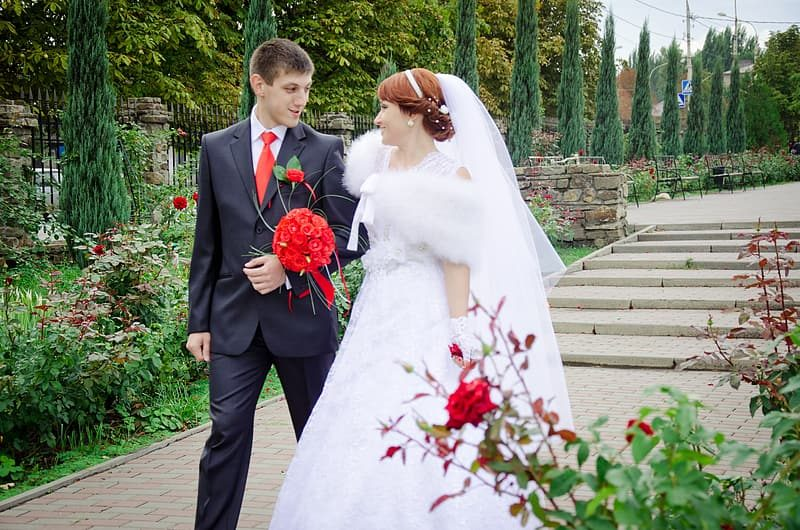 woman-in-wedding-gown-holding-bouquet-of-red-roses-2019438